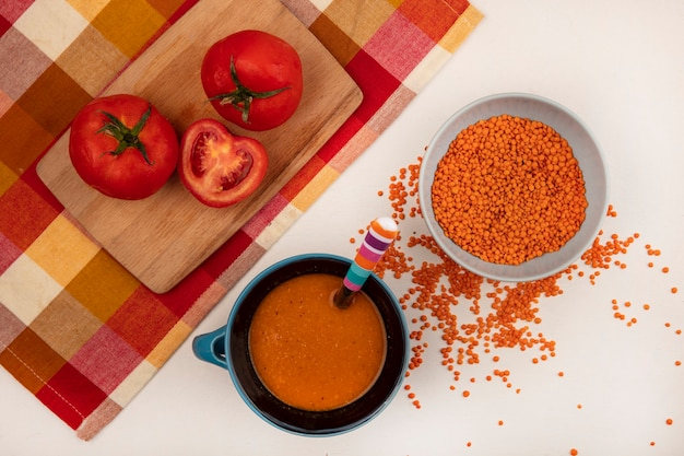 Top view of fresh lentils on a bowl with orange lentil soup on a bowl with tomatoes on a wooden kitchen board on a checked cloth on a white background