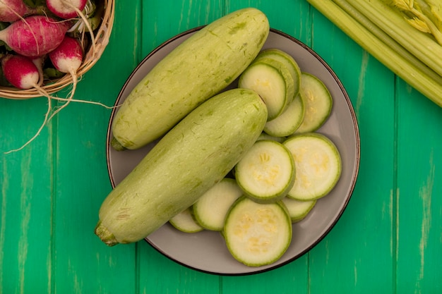 Top view of fresh light green zucchinis on a plate with radishes on a bucket with celery isolated on a green wooden wall