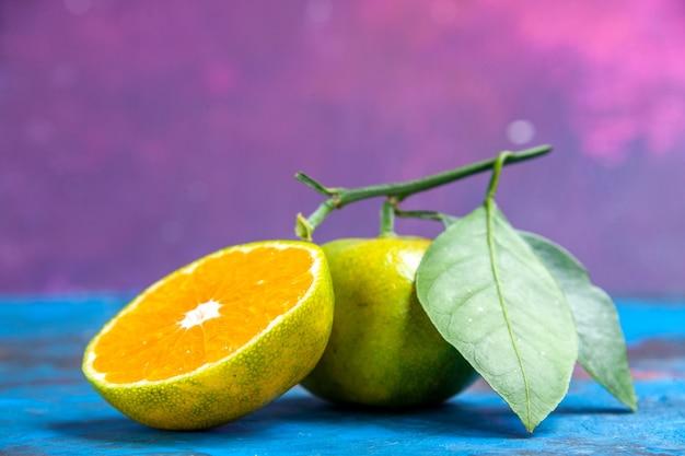 Vista dall'alto mandarino fresco con foglie e mandarino tagliato su spazio libero superficie rosa blu