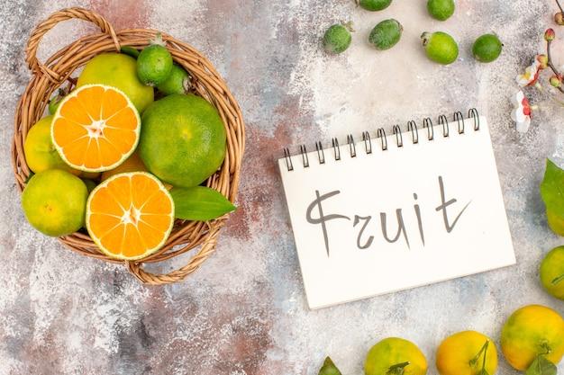 Top view fresh mandarines in a basket mandarines feykhoas fruit written on notepad on nude background