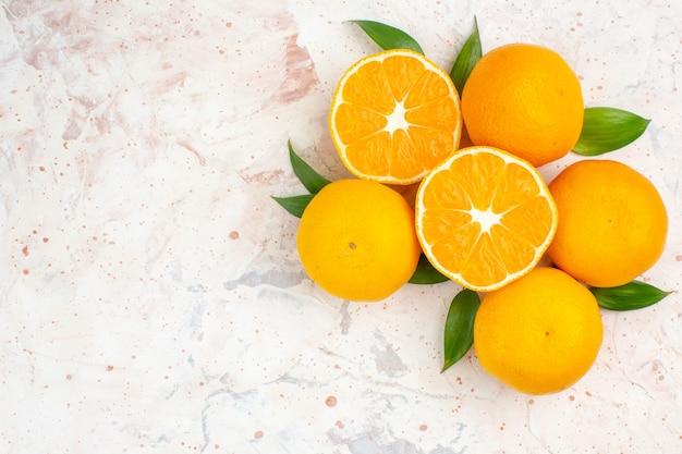 Mandarini freschi vista dall'alto sulla superficie isolata luminosa con posto libero