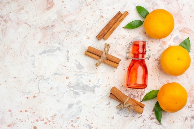 Vista dall'alto mandarini freschi bastoncini di cannella bottiglia sul posto libero superficie luminosa