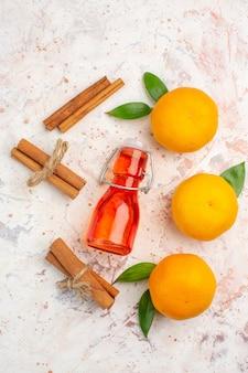 Vista dall'alto mandarini freschi bastoncini di cannella bottiglia sulla superficie luminosa