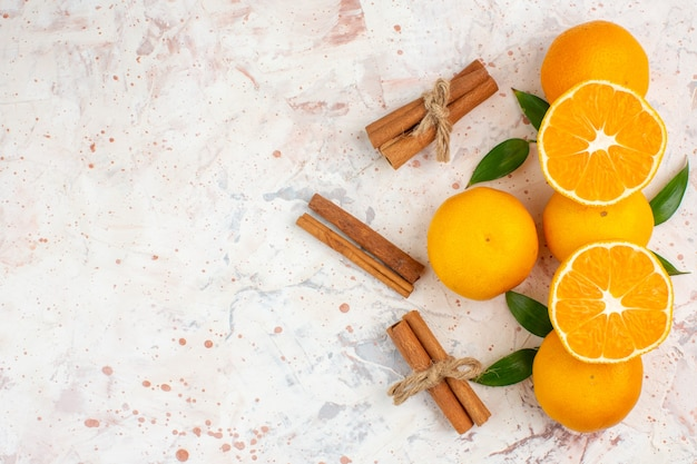 Top view fresh mandarines cinnamon sticks on bright isolated surface free place