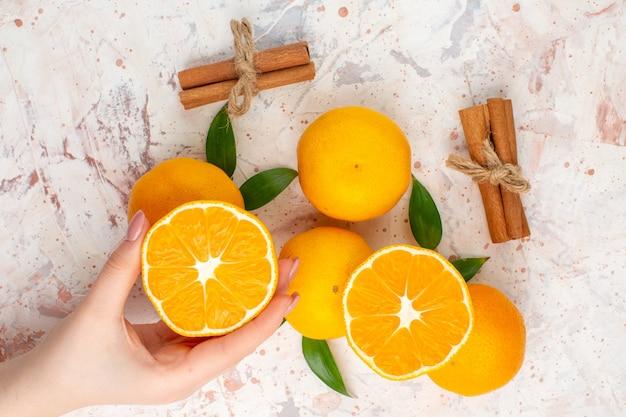 Вид сверху свежие мандарины, палочки корицы, нарезанный мандарин в руке женщины на яркой изолированной поверхности