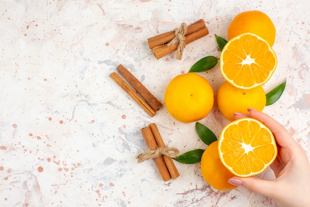 Top view fresh mandarines cinnamon sticks cut mandarine in woman hand on bright isolated surface free place