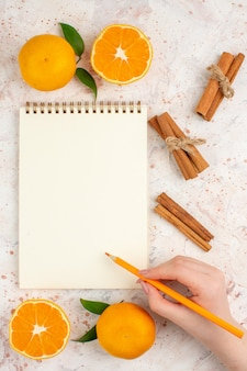 Top view fresh mandarines cinnamon sticks notepad pencil in woman hand on bright isolated surface