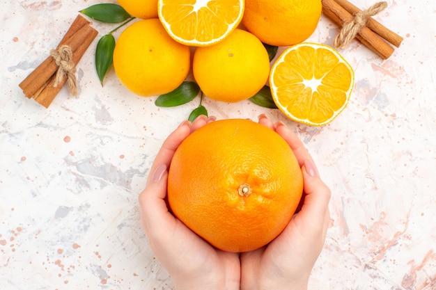Vista dall'alto mandarini freschi bastoncini di cannella arancione nelle mani della donna sulla brillante superficie isolata