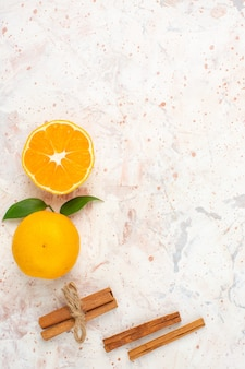 Top view fresh mandarines cut mandarine cinnamon sticks on bright isolated surface with free space