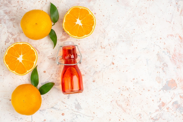 Top view fresh mandarines cut mandarines bottle on bright isolated surface with free space