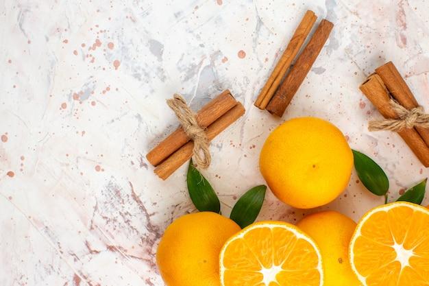 Top view fresh mandarines cut mandarines cinnamon sticks on bright isolated surface free place