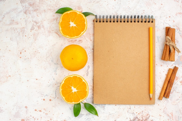 Top view fresh mandarines cut mandarines cinnamon sticks pencil on notebook on bright isolated surface with free space