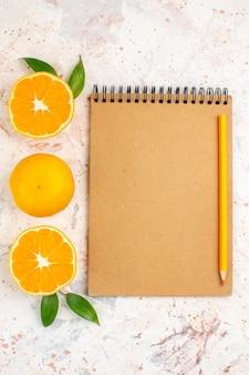 Top view fresh mandarines cut mandarines cinnamon sticks pencil on notebook on bright isolated surface