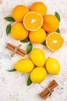 Top view fresh mandarines lemons cinnamon sticks on bright isolated surface