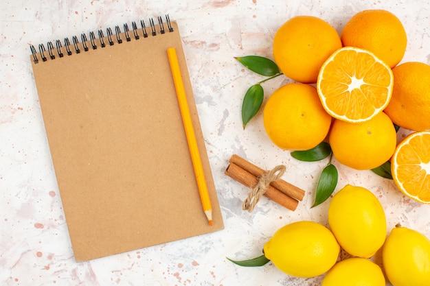 Top view fresh mandarines lemons cinnamons notepad pencil on bright surface