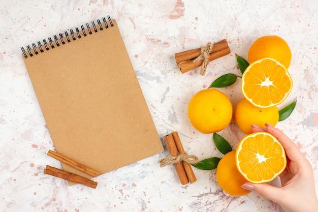 Top view fresh mandarines notebook cinnamon sticks cut mandarine in woman hand on bright isolated surface