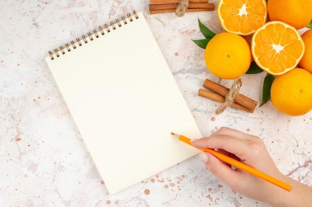 Вид сверху свежие мандарины блокнот палочки корицы карандаш в женской руке на яркой изолированной поверхности