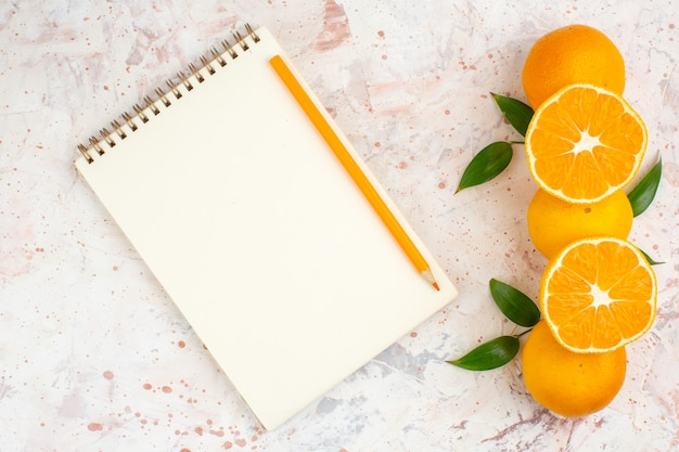 Top view fresh mandarines notepad orange pencil on bright isolated surface