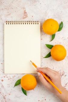 明るい孤立した表面上の女性の手で新鮮なマンダリンメモ帳鉛筆の上面図