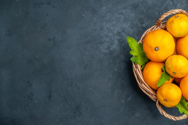 Top view fresh mandarines in wicker basket on dark background free place