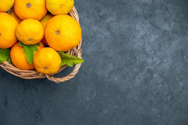 Mandarini freschi di vista superiore in canestro di vimini su fondo scuro