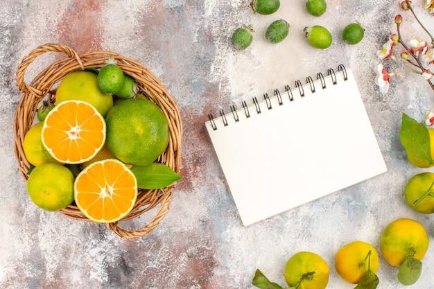 Top view fresh mandarines in wicker basket mandarines feykhoas notepad on nude background