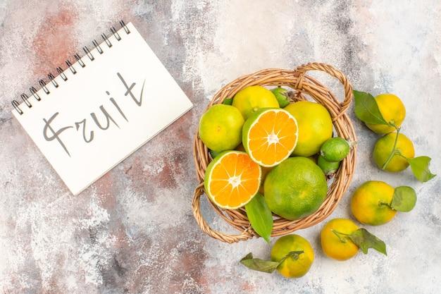 Vista dall'alto di mandarini freschi in cesto di vimini circondati da frutti di mandarini scritti su un taccuino su sfondo nudo