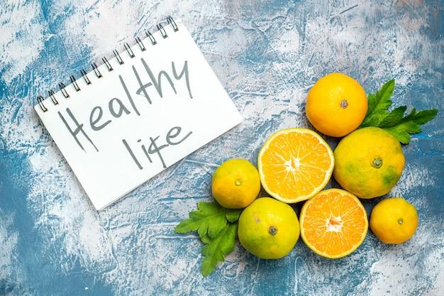 Vista dall'alto mandarini freschi tagliati mandarini vita sana scritta sul blocco note sulla superficie bianca blu