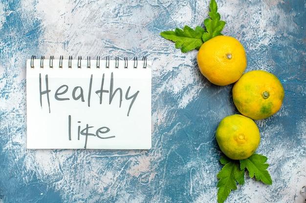 Vita sana dei mandarini freschi di vista superiore scritta sul blocco note sulla superficie bianca blu