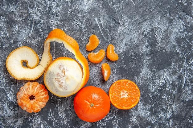 Top view fresh mandarins peeled mandarins on grey background with free space