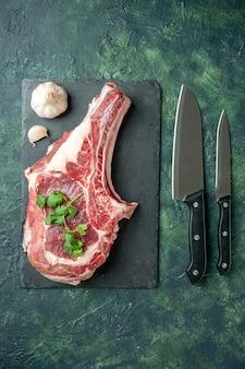 Fetta di carne fresca vista dall'alto con coltelli su sfondo blu scuro cucina cibo mucca macellaio carne pollo colore