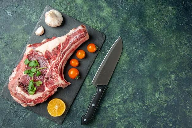 紺色の背景にオレンジ色のトマトと新鮮な肉のスライスの上面図食品肉キッチン動物鶏色牛肉屋