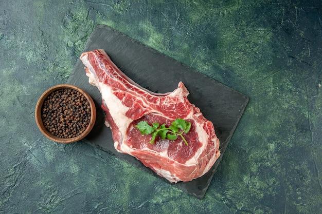 Vista dall'alto fetta di carne fresca con pepe su sfondo blu scuro cucina animale mucca pollo colorante macellaio carne