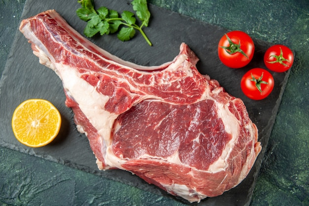 Top view fresh meat slice with red tomatoes on a dark-blue background kitchen animal cow food butcher meat chicken color