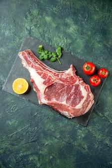 Fetta di carne fresca vista dall'alto con pomodori rossi su sfondo blu scuro cucina animale mucca cibo macellaio carne pollo colori