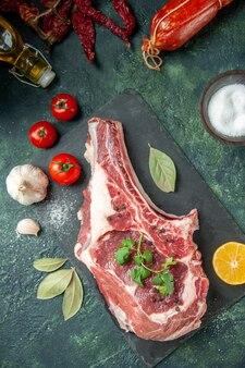 上面図紺色の背景に赤いトマトと新鮮な肉のスライスキッチン動物牛料理肉屋肉鶏肉色