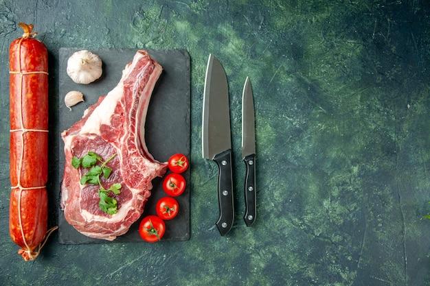 Vista dall'alto fetta di carne fresca con salsiccia su sfondo blu scuro carne cucina animale mucca cibo macellaio pollo colore