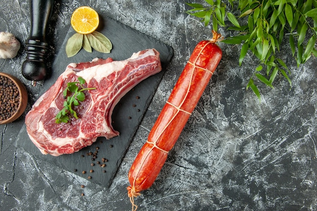 Top view fresh meat slice with sausage on light-gray background kitchen animal cow chicken meat food color butcher