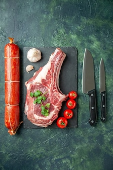 紺色の背景にソーセージを添えた新鮮な肉のスライスの上面図肉キッチン動物牛料理肉屋チキンカラー