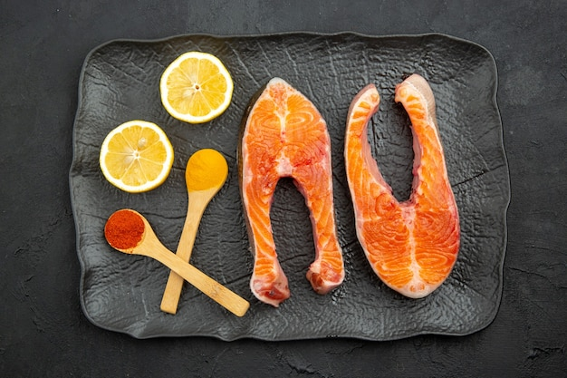 暗い背景にレモンとプレート内の新鮮な肉のスライスの上面図