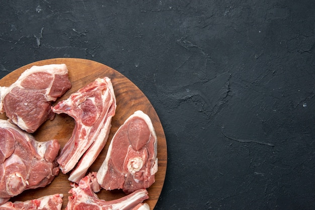 上面図新鮮な肉は、暗い食品の鮮度牛の食事食品キッチンの丸い木製の机の上に生肉をスライスします