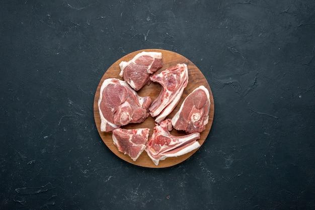 Vista dall'alto fette di carne fresca carne cruda su scrivania in legno rotonda su cibo scuro freschezza animale pasto cucina di mucca