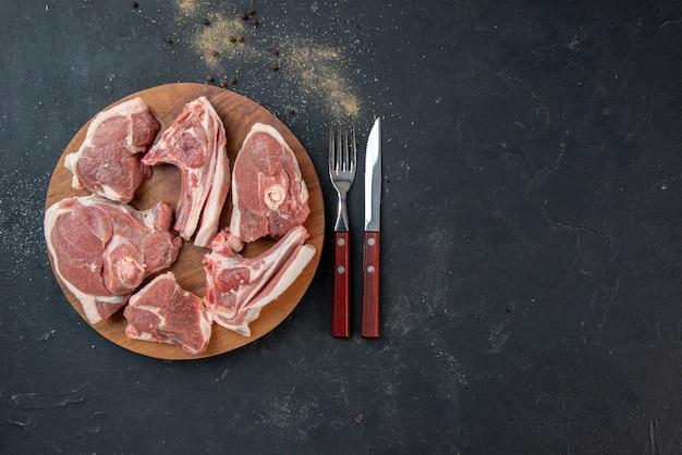 上面図新鮮な肉は、暗いキッチンサラダミールフード牛フード動物料理にフォークとナイフで生肉をスライスします
