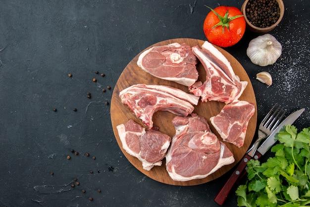 Vista dall'alto fette di carne fresca carne cruda con verdure e pomodori su cibo da cucina scuro cibo per mucche piatto per insalata animale
