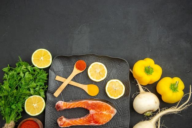 Fette di carne fresca vista dall'alto con limone verde e condimenti su sfondo scuro