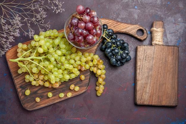 Vista dall'alto uva fresca e dolce su pavimento scuro vino uva fresca pianta da frutto matura