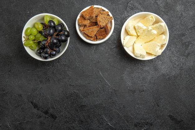 上面図暗い表面の食品ミールミルクフルーツにパンとチーズを添えた新鮮なまろやかなブドウ