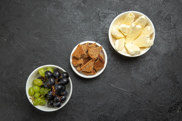 Top view fresh mellow grapes with bread and cheese on the dark surface food meal milk fruit