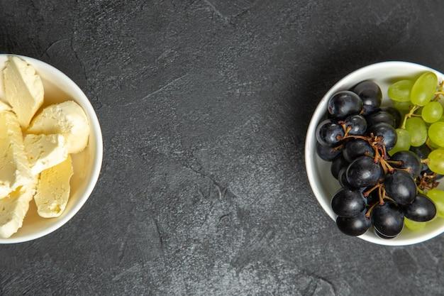 Vista dall'alto uva fresca e dolce con formaggio bianco su superficie scura pasto alimentare frutta latte