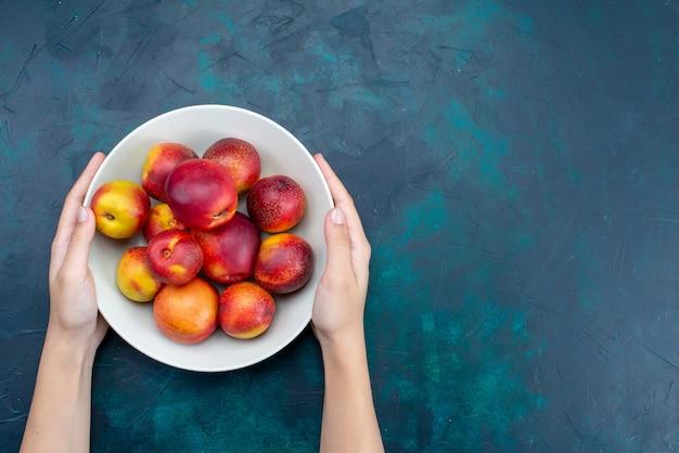 上面図紺色の机の上のプレートの内側の新鮮なまろやかな桃フルーツ新鮮な熟したまろやかなビタミン